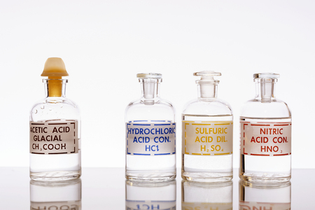 Foto de The three common inorganic acids and the most common organic acid used in chemistry: hydrochloric, sulfuric, nitric and acetic. - Imagen libre de derechos