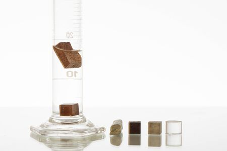 Photo pour Density of 2 different materials in a graduated cylinder. One object floating and one sinking. - image libre de droit