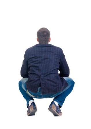Sitting young man looking afar. Rear view. Isolated over white.