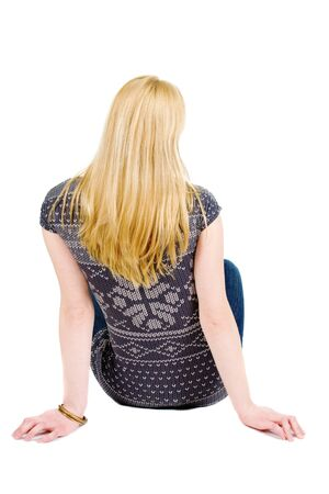 Back view of beautiful woman relaxes and looks into the distance. Blonde young girl sitting. Rear view people. Isolated over white background.の写真素材