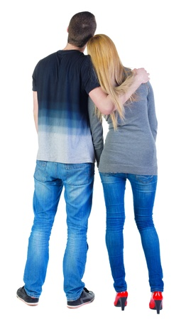 Back view of young couple (man and woman) hug and look into the distance. beautiful friendly girl and guy in shirt and jeans together. Rear view people collection.  backside view of person.  Isolated over white background.の写真素材