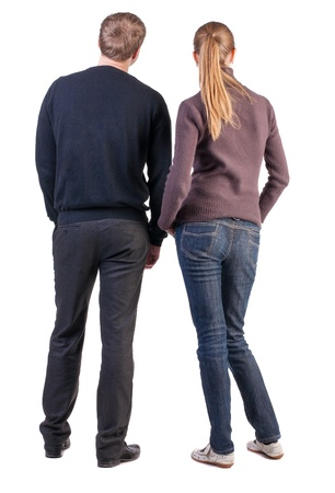 Back view of young couple (man and woman) hug and look into the distance. beautiful friendly girl and guy together. Rear view. Isolated over white background. a boy and a girl from opposite-sex couples face with his hands in his pockets and looking at somの写真素材