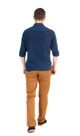 Foto de Back view of going  handsome man in jeans and a shirt.  walking young guy . Rear view people collection.  backside view of person.  Isolated over white background.  man in brown pants, shirt sleeves rolled away into the distance. - Imagen libre de derechos