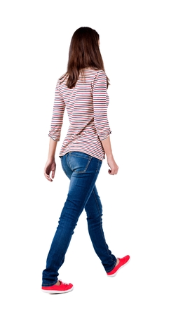 Photo pour back view of walking  woman in jeans . beautiful brunette girl in motion.  backside view of person.  Rear view people collection. Isolated over white background. The girl in a striped T-shirt with sleeves podkatannymi goes ahead - image libre de droit