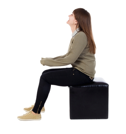 Photo pour back view of young beautiful  woman sitting.  girl  watching. Rear view people collection.  backside view of person.  Isolated over white background. The girl is sitting on a leather ottoman and smiling. - image libre de droit