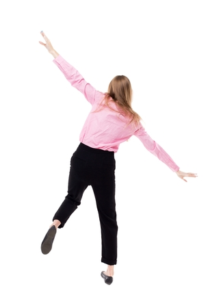 Balancing young business woman.  or dodge falling woman. Rear view people collection.  backside view of person.  Isolated over white background. The girl office worker in black pants balances on the left leg waving his arms.