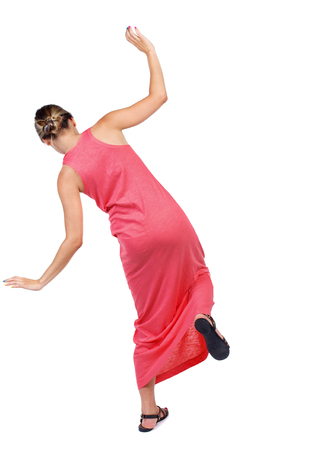 Balancing young woman.  or dodge falling woman. Rear view people collection.  backside view of person.  Isolated over white background. A slender woman in a long red dress is trying to stand on the leg.