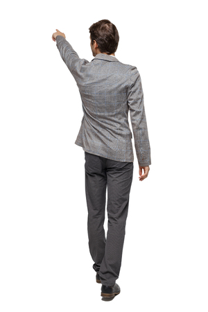 Foto de Back view of walking pointing business man. gesticulating young guy in suit. Rear view people collection.  backside view of person.  Isolated over white background. A young businessman in a tweed suit conducts a tour. - Imagen libre de derechos