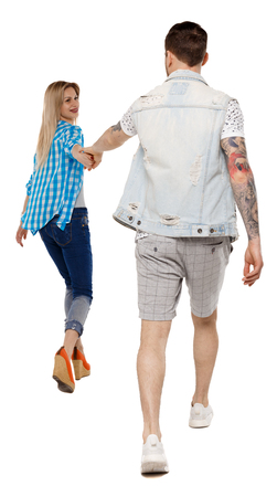 Foto de Back view of going couple. walking friendly girl and guy holding hands. Rear view people collection. backside view of person. Isolated over white background. Happy girl pulls the hand of her boyfriend. - Imagen libre de derechos