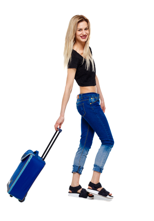 Photo pour Side view of walking woman with suitcase. girl in motion. backside view of person. Rear view people collection. Isolated over white background. Happy blonde rolls a suitcase. - image libre de droit