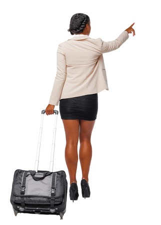 Photo pour Back view of a black African-American in formal attire walking with a suitcase and pointing hand forward. business woman in motion.  backside view of person.  Rear view people collection. Isolated over white background. Black business woman leaves showing hand up. - image libre de droit