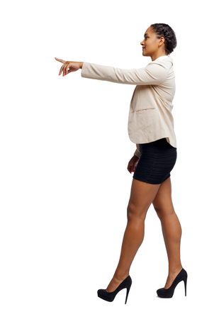 Photo pour Side view of a black African-American in a suit that goes and points with his hand. backside view of person.  Rear view people collection. Isolated over white background. - image libre de droit