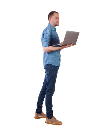 Photo pour Back view of a man who is standing with a laptop. Rear view people collection.  backside view of person.  Isolated over white background. A young engineer checks information with a laptop. - image libre de droit
