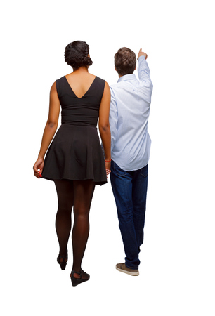 Photo for Back view of interracial going couple who points somewhere. walking friendly girl and guy holding hands. Rear view people collection. backside view of person. Isolated over white background. Guy and girl on an excursion or exhibition. - Royalty Free Image