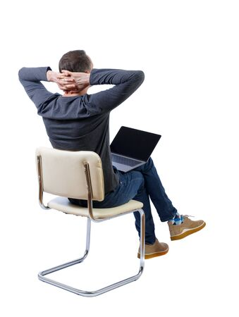 Photo pour Back view of a man who sits on a chair with a laptop. Rear view people collection. backside view of person. Isolated over white background. A man in a gray jacket sits on a white chair with a laptop, his hands behind his head. - image libre de droit