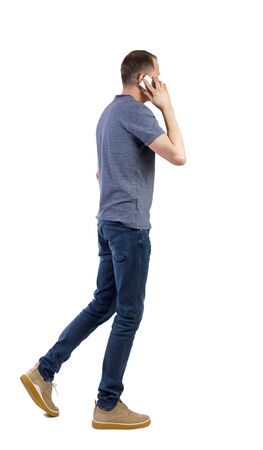 Photo pour a side view of man walking with a mobile phone. backside view of person. Rear view people collection. Isolated over white background. - image libre de droit