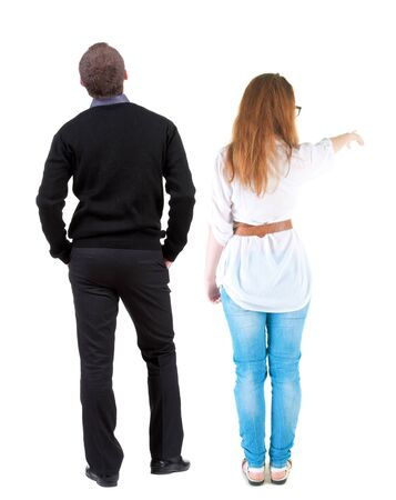 Photo pour Back view of a stylish couple pointing. beautiful friendly girl and guy together. Rear view people collection. backside view of person. Isolated over white background. - image libre de droit