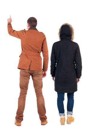 Photo pour Back view of couple couple in winter jackets pointing. beautiful friendly girl and guy together. Rear view people collection. backside view of person. Isolated over white background. - image libre de droit