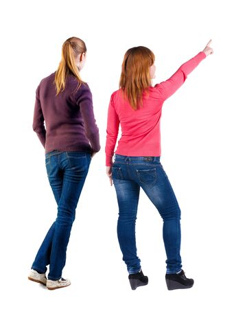 Photo pour Back view of two pointing young girl in sweater. Rear view people collection. backside view of person. beautiful woman friends showing gesture. Rear view. Isolated over white background. - image libre de droit