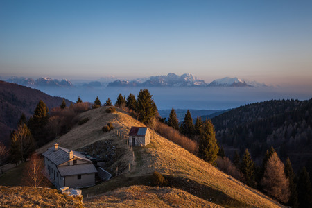 Sunrise on a small hut with in the background the dolomite peaks and Belluno Valley, Pian de le Femene, Veneto, Italy