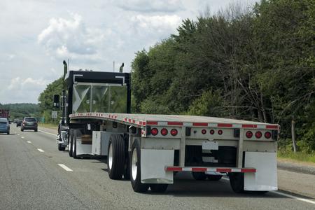 Foto de Rear view of empty flatbed trailer on highway. - Imagen libre de derechos