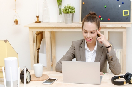 asian young business woman beautiful smile working on laptop computer on wooden desk, soft focus, sunlight effect, social network media technology, business lifestyle and working woman concept