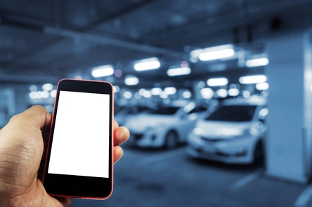 Photo for hand using mobile smart phone with blank screen for text with blurred image of underground car parking garage area background, internet, technology and searching information concept, blue color tone - Royalty Free Image