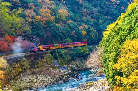 Foto de beautiful mountain view in colorful autumn season with sagano scenic railway or romantic train on bridge and boat in the river in Arashiyama, Kyoyo, Japan - Imagen libre de derechos