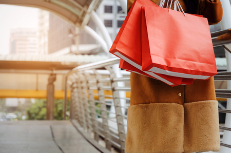 midsection beautiful cheerful asian holding many colorful red shopping bags walking in modern big city, fashion, promotion, special offer, winter sale, people, payment and shopping online concept