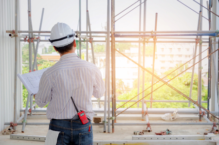 Foto de back view of smart engineer, architect or technician with white safety helmet holding blueprint in construction site building to greeting start up project, successful, business, industry concept - Imagen libre de derechos