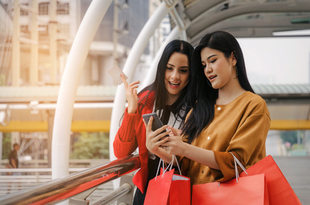 two beautiful cheerful asian and caucasian young woman with mobile smart phone, credit card and holding shopping bags together walking in modern city, sale, people, payment and shopping online concept