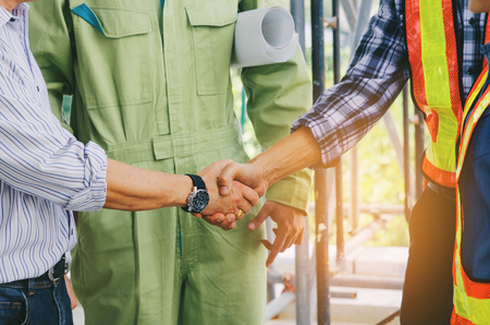 Photo pour midsection of team of engineer and technician contractor shaking hands after finishing up business meeting - image libre de droit