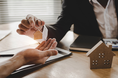Photo pour real estate broker manager giving house key to customer after signing contract for buying house in estate agent office, investment, home loan contract, buying house, real estate and insurance concept - image libre de droit