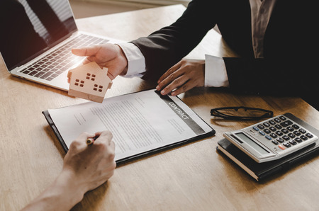 Photo pour real estate broker manager giving wooden house model to customer after signing contract for buying house in estate agent office, investment, home loan contract, selling house, real estate concept - image libre de droit