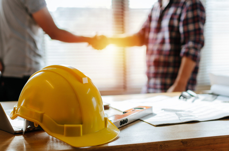 Foto de yellow safety helmet on workplace desk with construction worker team hands shaking greeting start up plan new project contract in office center at construction site, partnership and contractor concept - Imagen libre de derechos