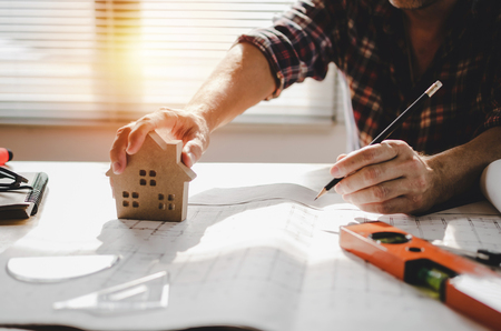 Photo pour professional architect, engineer or interior hands drawing with house model design and blueprint on workplace desk in office center at construction site, contractor, construction, engineering concept - image libre de droit