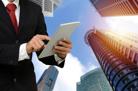 Photo pour young handsome business man in suit reading information about finance news with mobile tablet with during sunrise and cityscape background, network technology, finance investment, partnership concept - image libre de droit