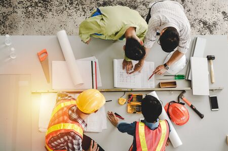 Foto de top view of group of engineer, technician and architect planning about building plan with blueprint and construction tools on the conference table at construction site, contractor and teamwork concept - Imagen libre de derechos