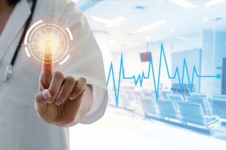 Photo pour hand of female doctor with stethoscope hand pointing touching virtual screen interface button with his finger and heartbeat rate line in hospital background, medical innovation technology concept - image libre de droit