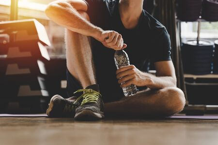 Foto de muscular caucasian young handsome man taking a break relax and drinking water while resting after workout for good healthy in fitness gym at morning, bodybuilder, lifestyle and sport exercise concept - Imagen libre de derechos