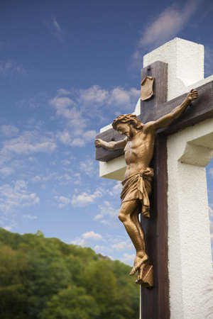 Statue of Jesus on cross with blue sky