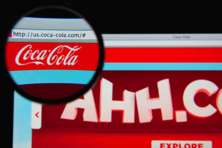 LISBON - JANUARY 19, 2014: Photo of Coca-Cola homepage on a monitor screen through a magnifying glass.