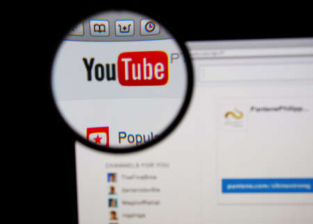 LISBON - JANUARY 14, 2014: Photo of Youtube homepage on a monitor screen through a magnifying glass.