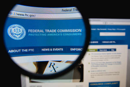 LISBON, PORTUGAL - FEBRUARY 8, 2014: Photo of the Federal Trade Commission homepage on a monitor screen through a magnifying glass.