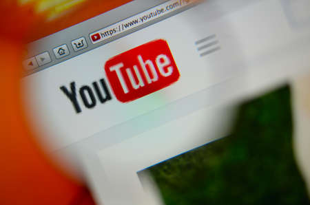 LISBON, PORTUGAL - AUGUST 3, 2014: Photo of Youtube homepage on a monitor screen through a magnifying glass.