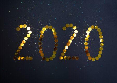 Photo pour Beautiful spakling golden number 2020 on black background for design. - image libre de droit
