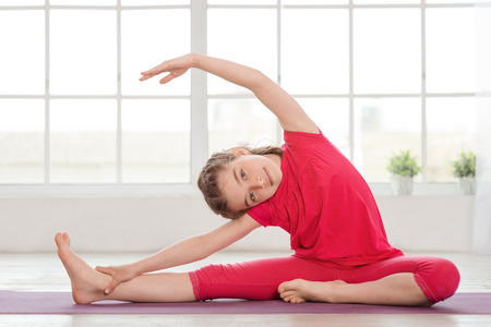 Foto de Little girl doing yoga exercise in fitness studio with big windows on background - Imagen libre de derechos