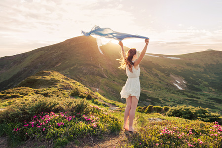 Woman feel freedom and enjoying the nature in the mountains with blue tissue in hands on sunset