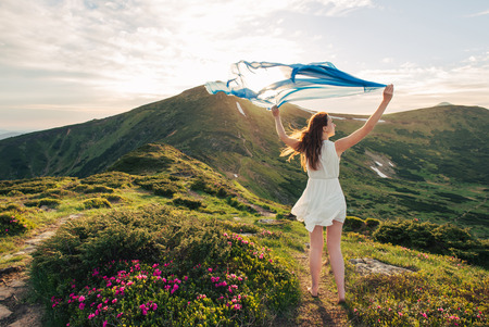 Photo pour Woman feel freedom and standing on the mountain trail through blooming rhododendron valley with blue tissue in hands on sunset - image libre de droit