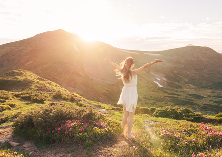 Foto de Happy woman enjoying the nature in the mountains and looking on sky with raised hands. Freedom concept - Imagen libre de derechos